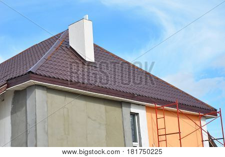Metal roof construction with chimney installation stucco plastering and painting house wall. Metal Roofing Construction with Plastic Soffits.