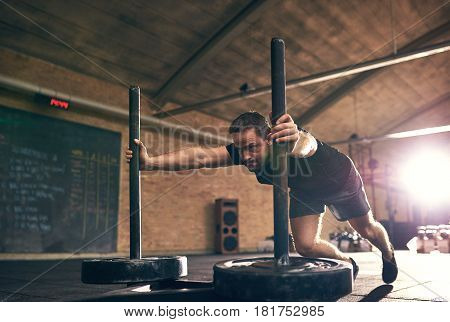 Sportive Man Pushing Weight Disks In Gym