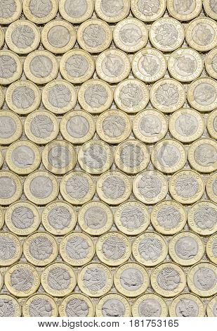 New pound coins background laid flat. Overhead point of view. The British bimetallic coin was introduced in March 2017.