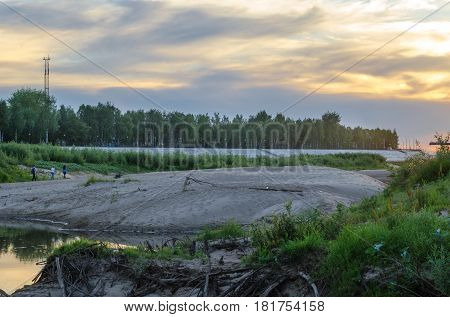 A small pond with sandy beaches and tree against a sunset summer sky