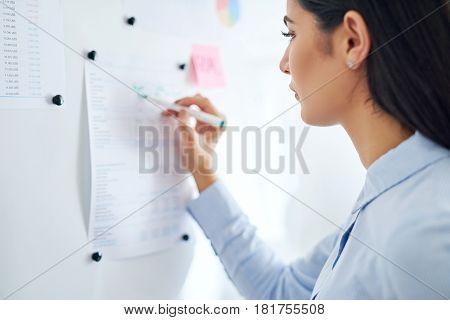 Woman Writing Information On Chart
