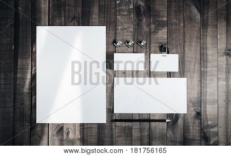 Blank stationery template for placing your design. Photo of blank stationery set on wood background. Blank letterhead business cards envelope badge and pencil. Mock up for branding identity. Top view.