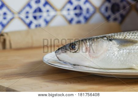 Mullet striped mullet contains omega-3 acids, vitamins and minerals. Mullet lying on the plate ready for cooking. A dietary product. Useful to reduce blood pressure.