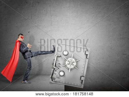 A businessman in a red superhero cape kicking at a giant strongbox to push it over the edge. Business and investment. Banking disadvantages. Business reliability.