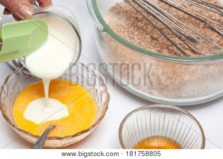 Wheat bran muffins preparation : Adding yogourt to the mix to prepare integral wheat bran muffins