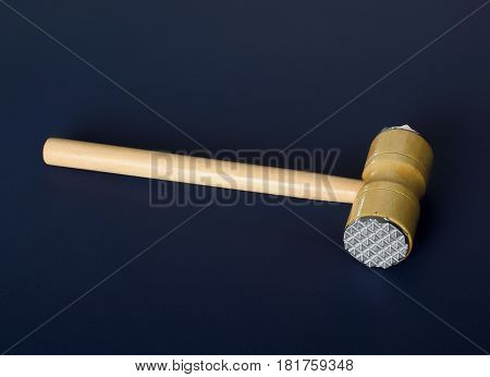 Hammer for beating the meat with a wooden handle. Meat tenderizer on blue background