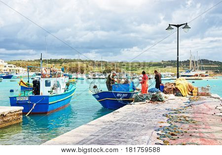 Fishermen On Luzzu Colored Boat At Marsaxlokk Harbor In Malta