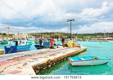 Fishermen On Luzzu Colored Boat At Marsaxlokk Harbor On Malta
