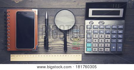 notebookpen reading glass and calculator on wooden table