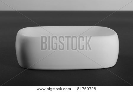 Empty white porcelain soap-dish on gray background