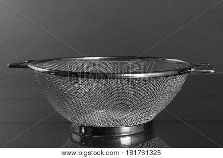 Empty strainer metal with handle blurred background. Front view