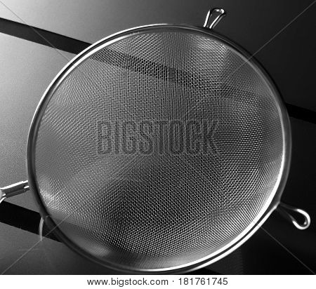 Close up of metal kitchen sieve on background