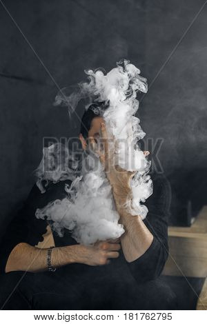 Vaping man holding a mod. A cloud of vapor. Black background. Smoking electronic cigarette Vape advertisement concept