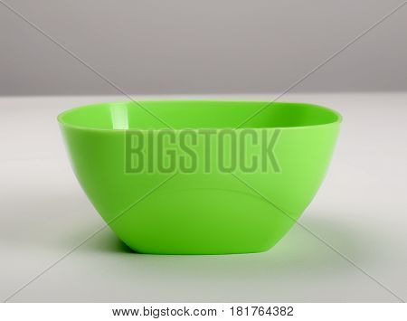 Green plastic deep dish on the table front view