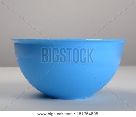 Blue plastic deep dish on the table, front view