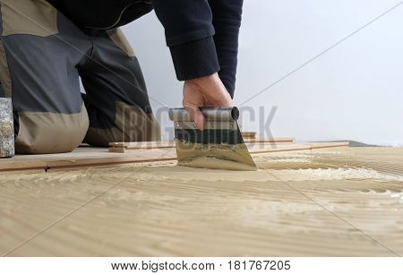 Worker applied adhesive for parquet. Home renovation