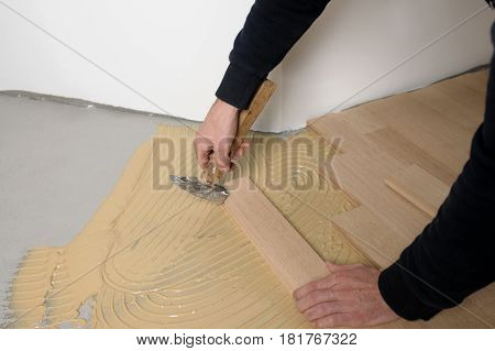 Worker installing wood parquet. Construction in a renovated room installation of parquet.