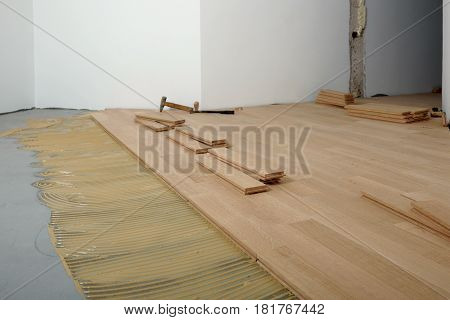 Construction in a renovated room installation of parquet.Pad applied with glue for parquet