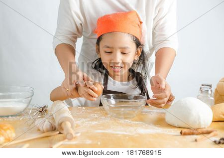 Close up shot of Asian little girl breaking the egg shell for make the bakery shallow depth of field focus on hand