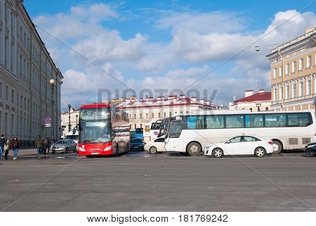 SAINT-PETERSBURG, RUSSIA, APRIL 15, 2017: Excursion buses and Hop On Hop Off City Tour Bus near The Palace Square and The State Hermitage Building in sunny April day