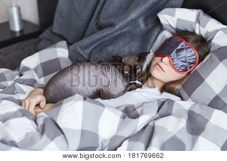 Two friends sphinx cat and young lady both in focus. Girl is sleeping in bed hiding from daylight with eye mask. Her cat is taking rest in her chest. Leasure relax lounge concept.