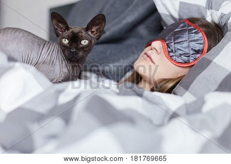 Close up portrait of girl and sphinx cat. Both in focus. Young beautiful lady is dozing wearing sleeping eye mask in her bedroom. Pet is watching out sideways carrying her dreams on her chest.