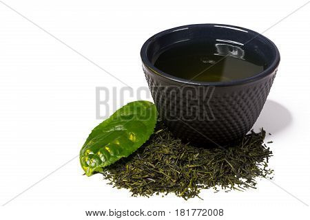 Iron cast cup and heap of green shincha tea first flush shadow tea with leaf isolated on white background..