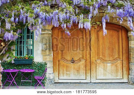Colorful Purple Tables Of Outdoor Parisian Cafe And Wisteria In Full Bloom