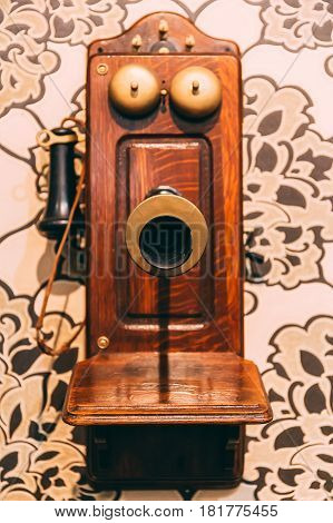 Wooden Vintage Telephone on the wall, selective focus on speaker and blurred phone