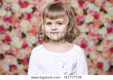 Portrait of a beautiful blonde little girl in white gown on a background of a flower wall in the studio