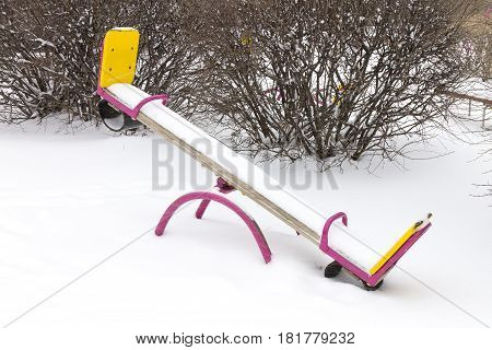 Children's seesaw covered in snow and frost on playground in winter
