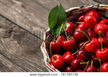 Sweet fresh cherries in basket on wood background
