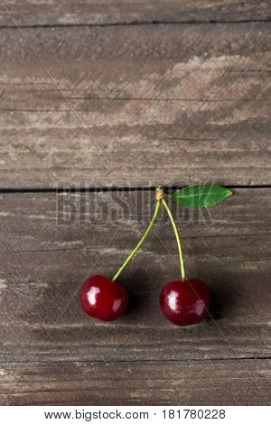 two fresh red cherries with leaf copy space