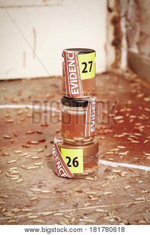Fly larva on crime scene in glass bottles