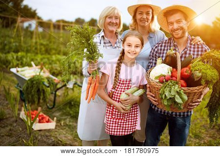 Rural family satisfied with their organic vegetables from garden