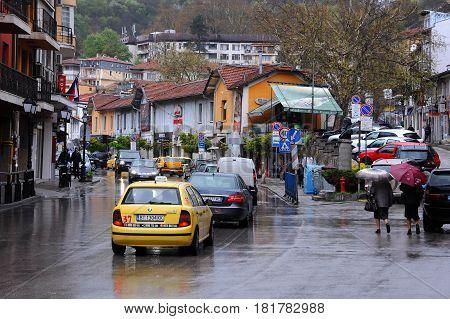 VELIKO TARNOVO BULGARIA - APRIL 8 2017: Cars and people downtown in the rain