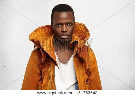 Studio Shot Of Handsome Young Dark-skinned Man Wearing Fashionable Orange Jacket With Hood, Looking