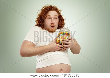 Portrait Of Chubby Red-haired Caucasian Man In Small White T-shirt Looking Ridiculous Clasping Glass