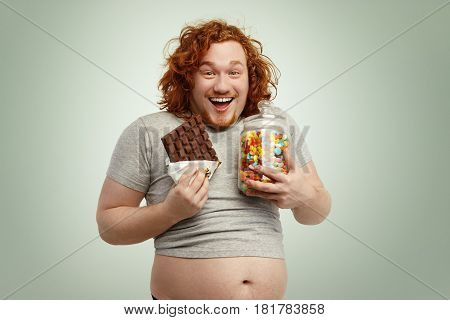 Portrait Of Happy And Joyful Red-haired Male Wearing Undersized T-shirt Standing At Blank Studio Wal