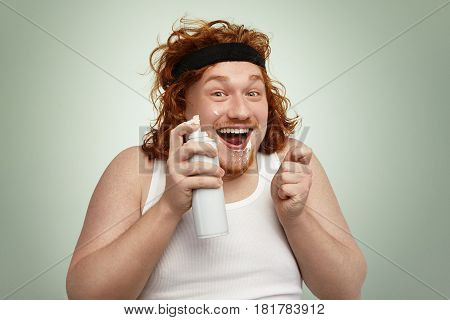 Cheerful Chubby Young European Man With Curly Ginger Hair Having Fun Indoors, Holding Spray Can, His