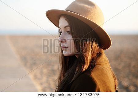 Thoughtful Young Brunette Woman Walking Along Boardwalk, Having Pensive Look, Came To Sea In The Eve