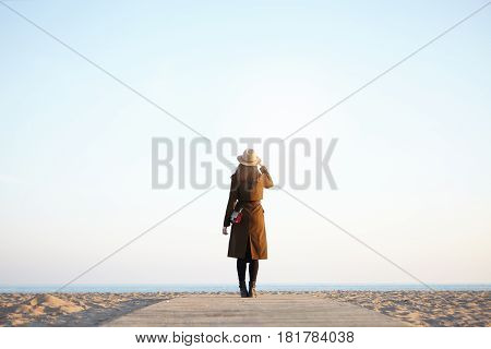 Outdoor Shot Of Woman Traveler Enjoying View Of Calm Sea Turned Back To Camera In Autumn Or Spring O
