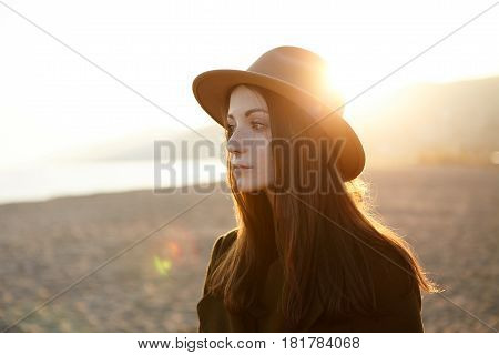Portrait Of Pensive And Melancholic European Girl Standing On Seacoast In Elegant Demi-season Outdoo