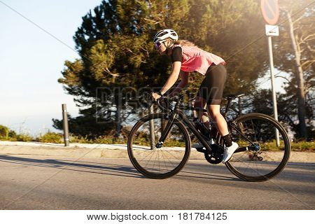 Side View Of Healthy Athletic European Woman Cycling Alone In Helmet And Sunglasses, Riding Bike At