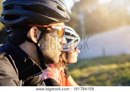 Cropped Portrait Of Two Cyclists In Helmets And Sunglasses Looking At Something While Riding Their B