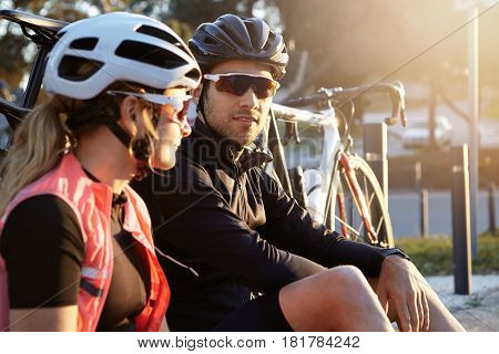 Side View Headshot Of Sportive And Healthy European Couple Sitting On Grass Near Their Bicycles In H