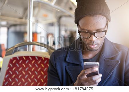 Attractive Young African American Tourist Wearing Black Hat, Stylish Glasses And Coat Using Smart Ph