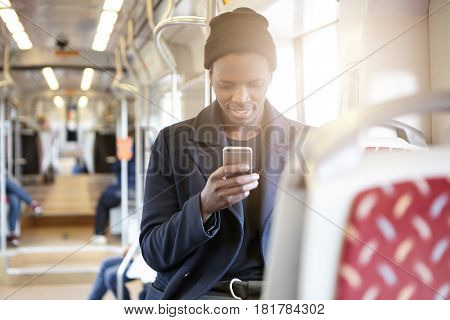 Portrait Of Fashionable African American Student Wearing Hipster Hat And Trendy Coat Checking Newsfe