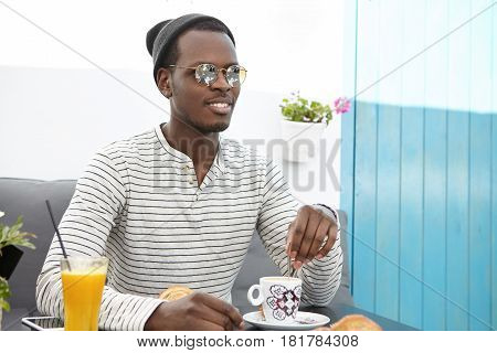 Fashionable Black Man In Round Sunglasses, Striped Shirt And Headwear Having Rest At Sidewalk Cafe,