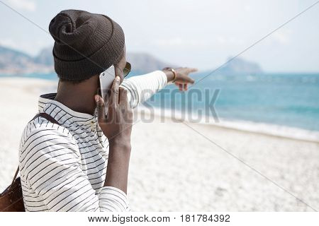 Unrecognizable Dark-skinned Young Male Tourist Dressed In Trendy Clothing Standing On White Sandy Be